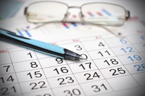 Workplace with calendar, pen and glasses work table
