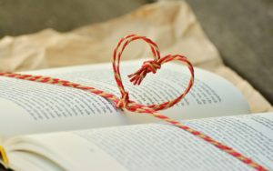 open book on plain wrap paper with red and beige string tied around with string heart on top