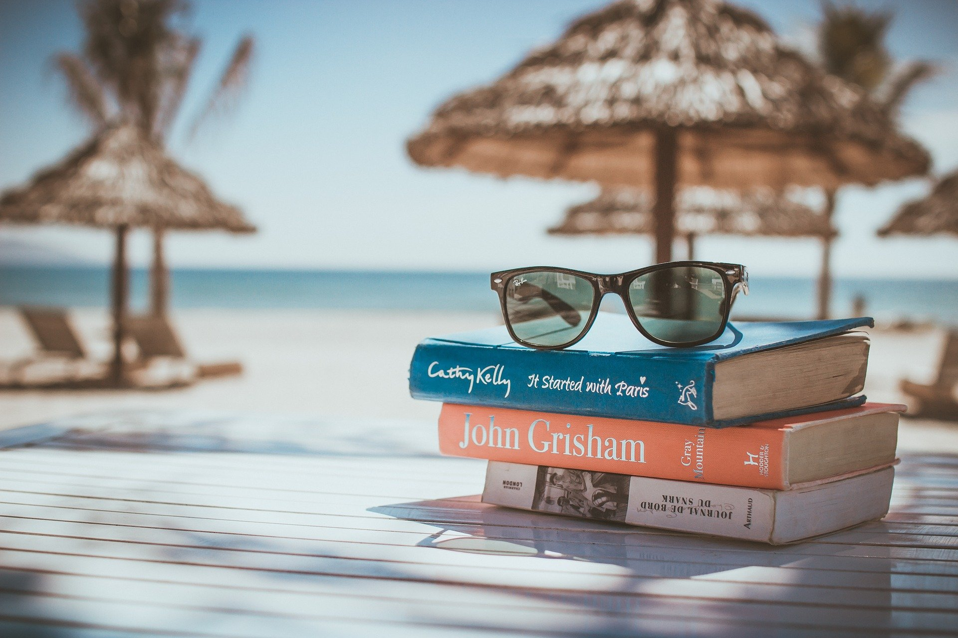 beach scene with sunglasses on top of pile of fiction books
